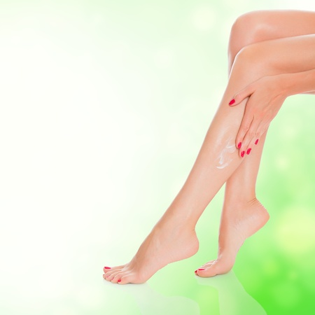 foot cream: Neat female legs with a body lotion, green blurred background