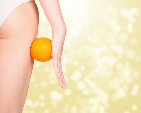 muslos: hermosa figura femenina con naranja, fondo dorado abstracto con un espacio para el texto o gráficos