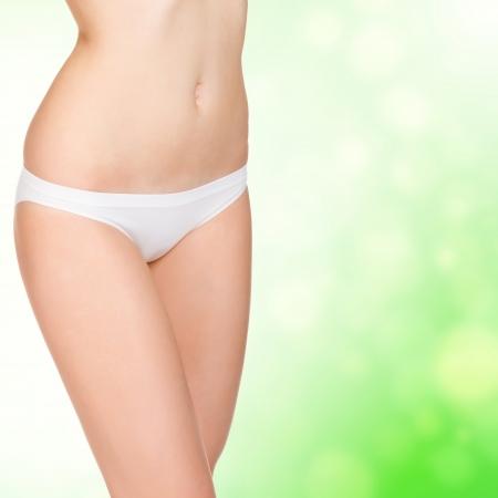 abdomen plano: mujer joven posando en bragas blancas sobre fondo verde enmascarado Foto de archivo