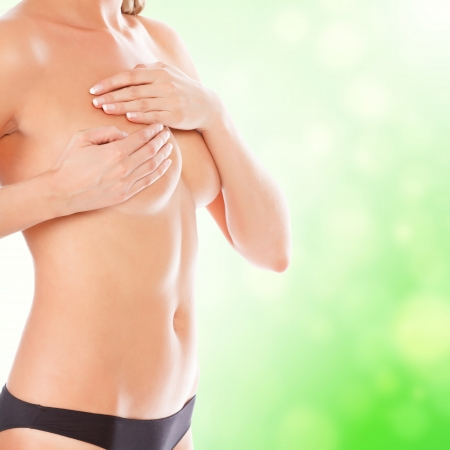 breasts erotic: Female controlling breast for cancer, green blurred background.  Stock Photo