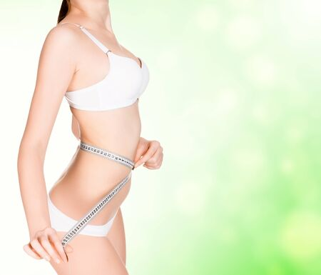 girl taking measurements of her body, green blurred background with a space for your message or graphics photo