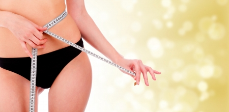 hands on waist: girl taking measurements of her body, gold blurry background with a space for your message or graphics