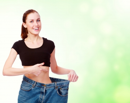 loose: attractive young woman shows her old huge pair of jeans, weight loss concept, green blurred background