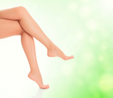 waxed: Perfect long female legs on green blurred background.  Stock Photo