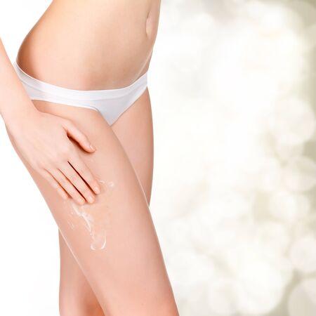 muslos: Mujer aplicaci�n de crema humectante en el cuerpo de cosm�tica, de oro borrosa de fondo con un espacio para su mensaje