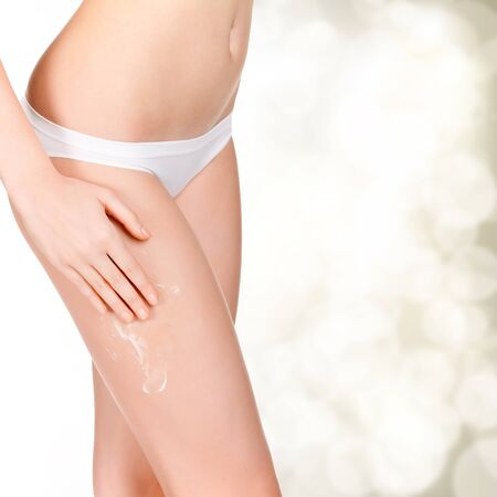 cellulite: Woman applying cosmetic moisturizer cream on body, golden blurred background with a space for your message