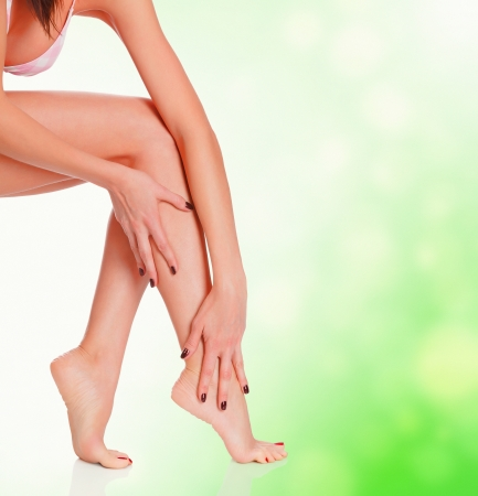 Female legs on green blurred background with a space for your text photo