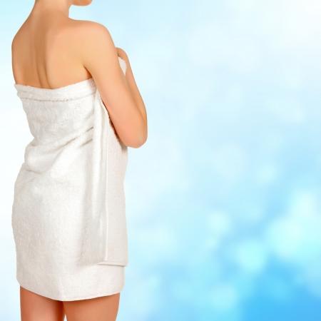 strandlaken: Vrouw gewikkeld in een witte handdoek, blauwe achtergrond wazig Stockfoto