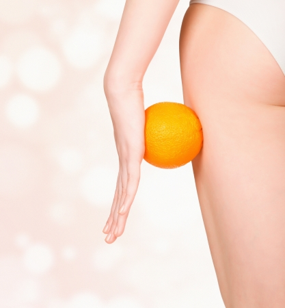 cellulite: beautiful female figure with an orange, pastel blurred background