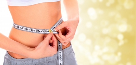 Woman taking measurements of her body on blurry background with copyspace photo