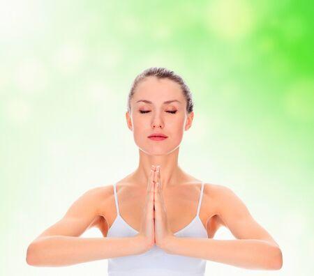 closed eye: young girl practicing yoga, meditating in prayer pose