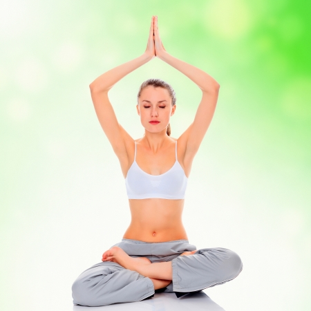 young girl practicing yoga, green blurred background Stock Photo - 14746698