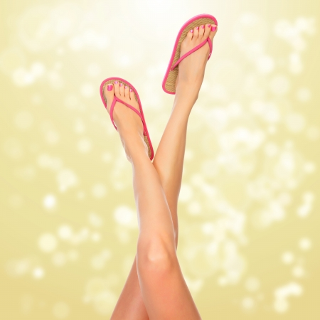Female legs with pink flip-flops, blurred lights on background photo