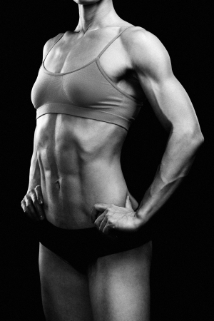 muscular: Muscular strong woman posing against a black background Stock Photo