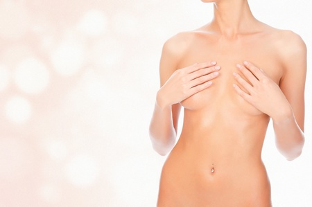 naked belly: Female body with a breast covered, pastel background with copyspace
