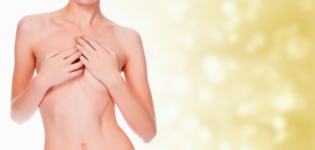 breast nipple: nude young female covering her breast with her hands, blurred pastel background