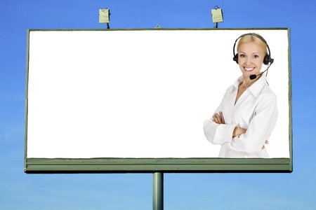 Woman wearing headset smiling to you from a big billboard photo