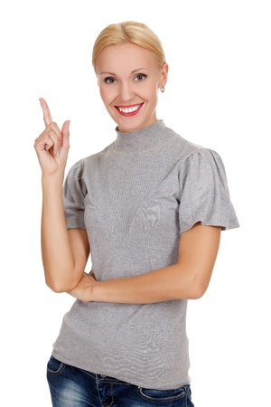 happy young woman pointing at something interesting against white background