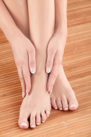 french pedicure: Well-groomed hands on female feet Stock Photo