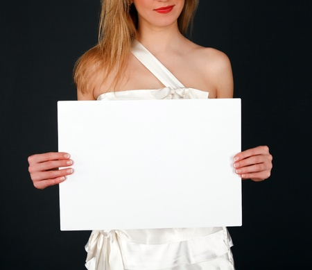 Bride shows white board with copyspace, black background photo