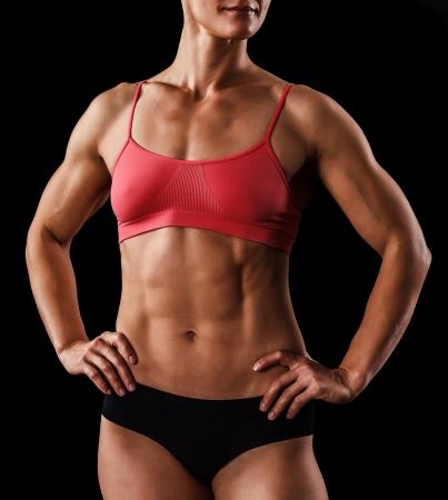 abdomen fitness: musculoso cuerpo femenino contra el fondo negro Foto de archivo