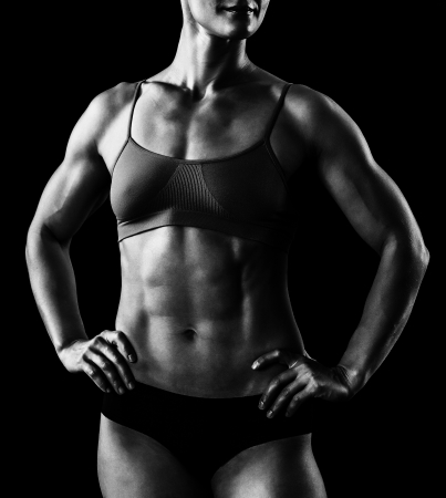 weightlifting: muscular female body against black background.