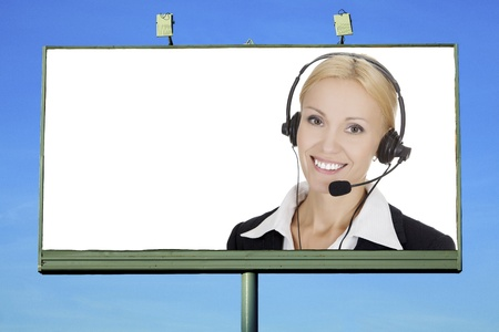 Pretty girl with headset smiling to you from street billboard with a space for your text  photo