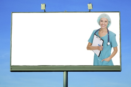 Pretty doctor smiling to you from billboard with a space for your info photo