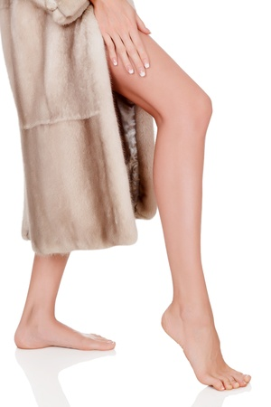 Woman in fur coat shows her leg, isolated on white background photo