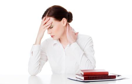 hoofdpijn: Vermoeide jonge vrouw aan een tafel met boeken, witte achtergrond