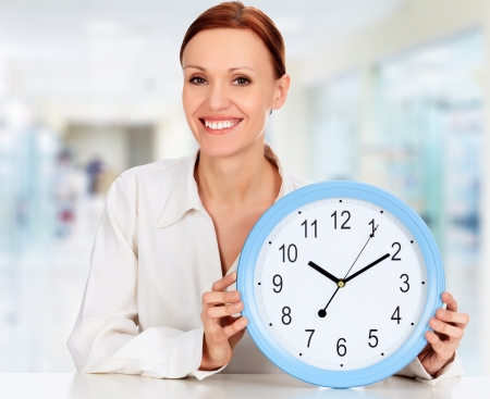 Time to break. Smiling woman with a clock in an office photo