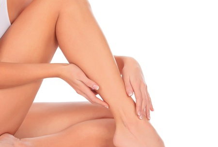 epilation: Woman sitting on the floor touches leg by hand, white background