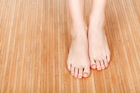 beautiful ankles: Female feet on a wooden floor Stock Photo