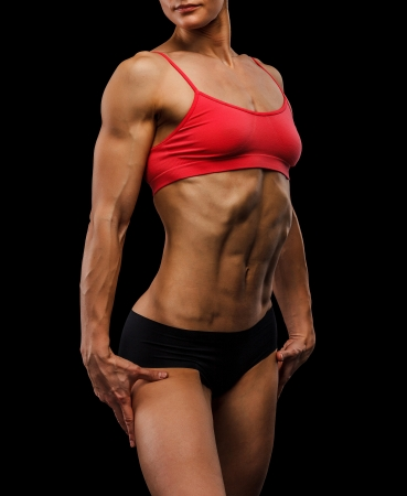 Muscular strong woman on a black background photo