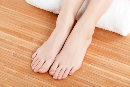 female feet with a white rolled towel  photo