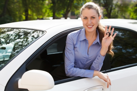 Pretty female driver in a white car showing the car key Stock Photo - 18793658