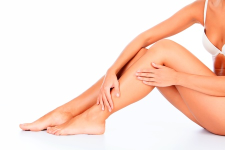 epilation: Woman sitting on the floor touches leg by hands, white background  Stock Photo