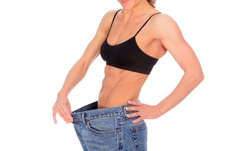abdomen plano: joven y bella mujer con una fuerte abdominales muestra sus viejos pantalones vaqueros grandes, aisladas en blanco