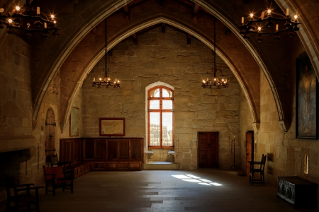 Dark old room in Poblet cloister with stained glass window and candelabra, Spain