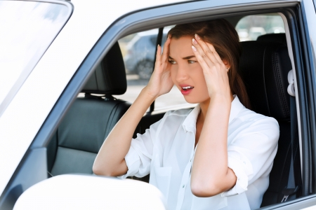 hysteria: Troubles on the road, girl touches her forehead by hands while in a car  Stock Photo