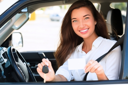 Happy girl in a car showing a key and an empty white card for your message  Imagens