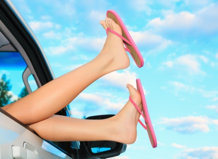 Female legs in pink sandals out from the car. Summer trip concept. photo