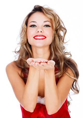 blow: Carino giovane donna in abito rosso che soffia un bacio a voi su sfondo bianco Archivio Fotografico
