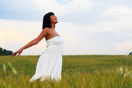 Young happy woman breathing fresh air in green field  photo