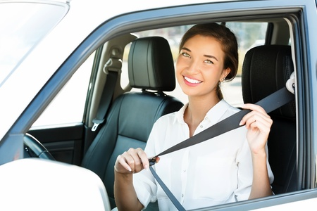 Attractive young woman in a car fastens seat belt photo