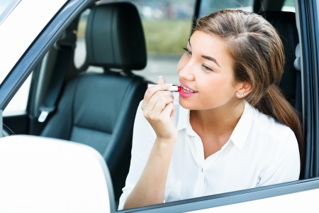Young woman applying makeup while in the car  photo