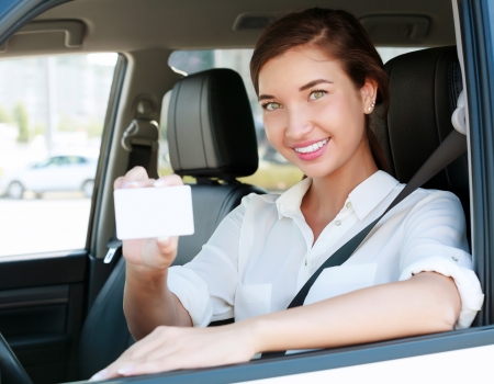 girl in a car showing an empty white card for your message photo