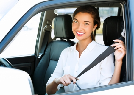 fastens: Attractive young woman in a car fastens seat belt