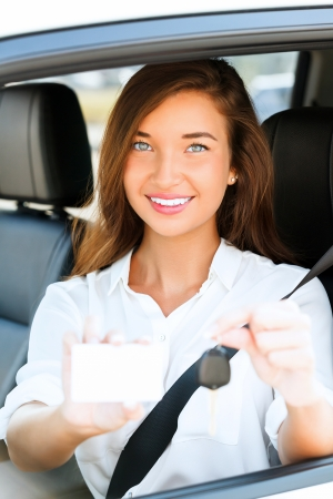 girl in a car showing a key and an empty white card  photo