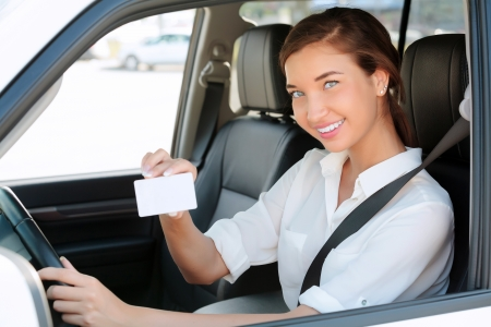 girl in a car showing an empty white card for your message  Zdjęcie Seryjne